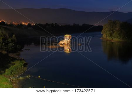 wooden house on river by night, Serbia