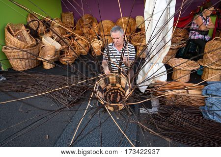CAMACHA MADEIRA PORTUGAL - SEPTEMBER 10 2016: A basket weaver at work in the factory shop in Camacha Madeira Portugal