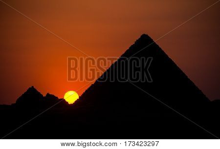 A sun sets in the crook between Menkaure pyramid and the queen's pyramids on the Giza Plateau, Cairo