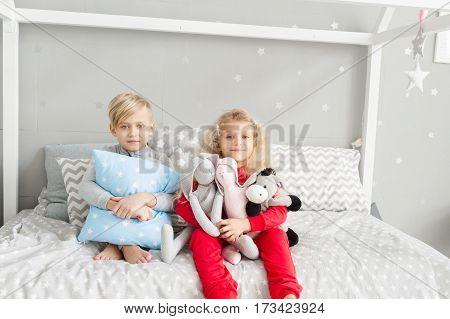 Little girl with white curly hair in red pajamas and a little boy with blond hair in a gray pajamas in the children's bedroom. Girl holding soft toys. Brother and sister