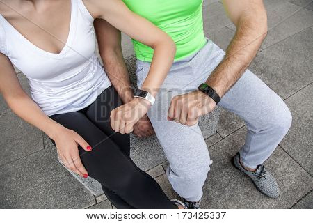 Two people using smart sport watch at workout.