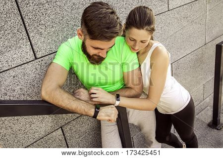 Young sporty couple are resting and check their fitness watch together. sport and technology concepts.