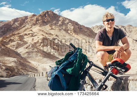 Young tourist man travel with bike in Himalaya montain