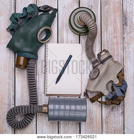 Two retro gas mask notebook and pen on light wooden table.Top view