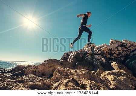Man runs on rocky sea side ю