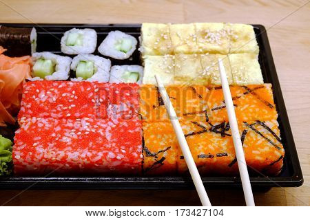Sushi pieces on square tray on brown wooden table front view closeup