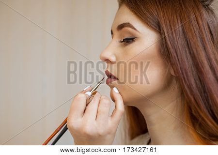 Makeup Artist Apply Makeup And Color Lipstick With A Professional Brush In A Beauty Salon. Professio