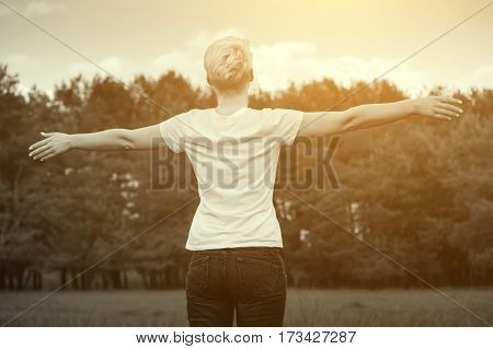Attractive young blonde girl with outstretched hands in the hand of a beautiful cloudy sky.