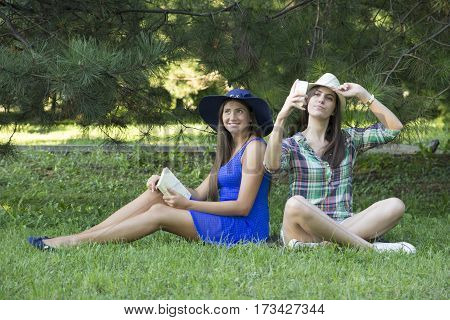 Girls In The Park With Book And Mobile Phone