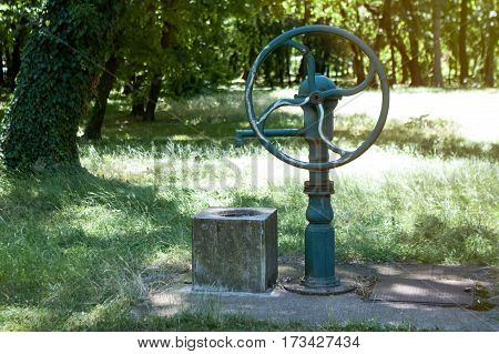 Old style green water well and pump for water