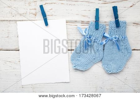 Baby socks hanging on white wooden background.