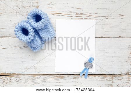 Greeting children form with blue booties on white wooden background