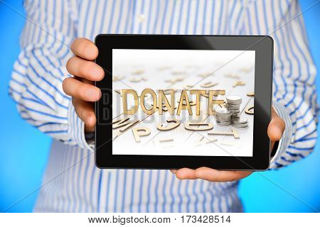Businessman showing black tablet computer with donate word on the screen.