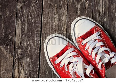 red sneakers on old wooden background.Toned image