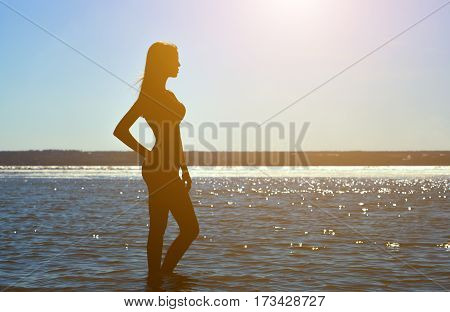 Silhouette Of A Beautiful, Slim Girl On A Background Of A Sunset On The Beach.