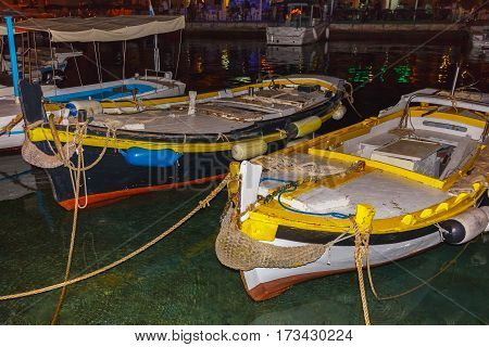 Small wooden fishing boats in marine at night