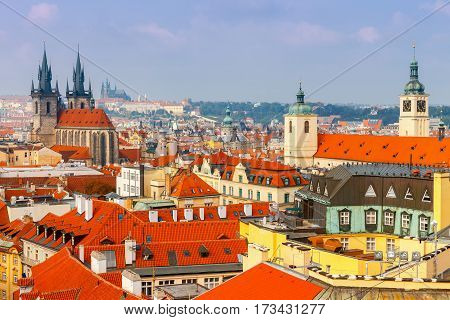 Aerial view of the historic center of Prague with towers spiers and red-tiled roofs.
