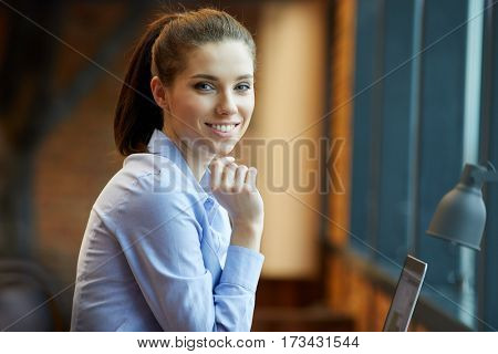 Beautiful, young woman with laptop working in office