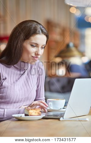 Beautiful brunette using laptop in cafe. Blogger work concept