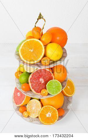 Different citrus fruit (orange lemon lime grapefruit kumquat) on cake stand on the white background