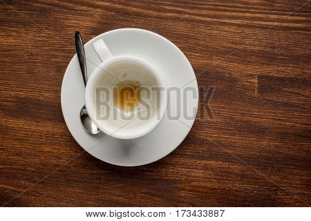 Empty coffee cup after drink on wood table. Top view.