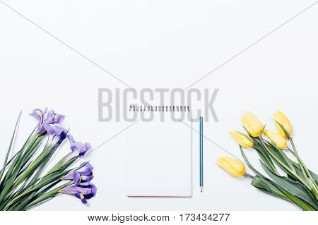 Lilac Irises, Yellow Tulips And Notepad With A Pencil On A White Table