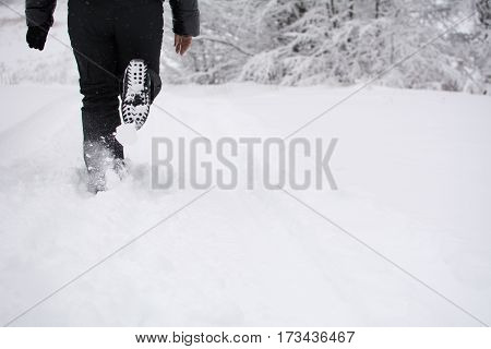 Woman running in the snow, on snow covered mountain. Winter landscape on Stara Planina mountain, Serbia.