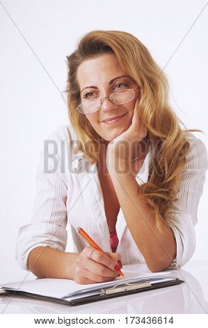 Businesswoman sitting in office and writing plan perfect day for superhuman productivity in his diary. (Time management success productivity work concept)
