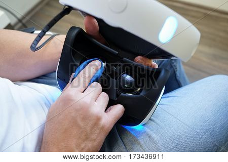 Man cleaning virtual reality glasses sitting on the chair in the room wearing white t-shirt and blue jeans top view. Male hands holding virtual reality goggles VR
