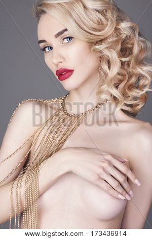Fashion beauty Nude blonde woman on a light background. Girl with jewels on the arms and neck. Skin care and beautiful makeup perfect girls. Luxury woman with elegant curly hair