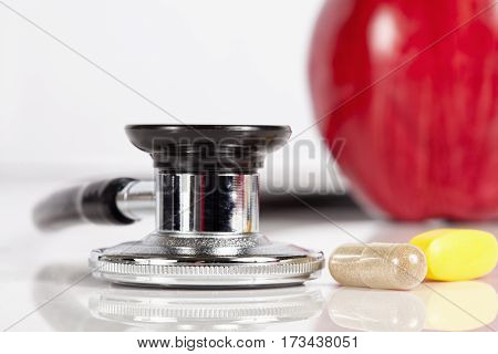 Macro photo of stethoscope, apple and pills.  Focus on the stethoscope.