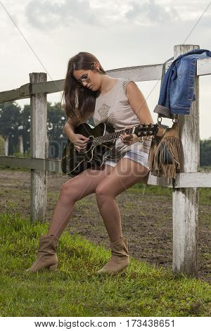 The beautiful girl with a guitar in the countryside Selective focus and small depth of field lens flare