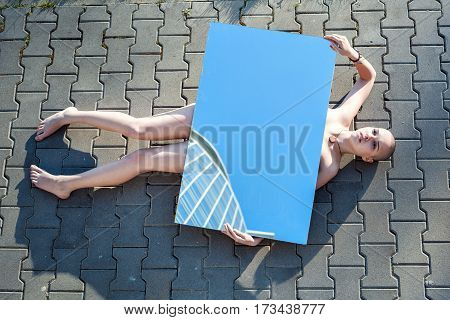 Strange young woman lying on the road with no signs of life.