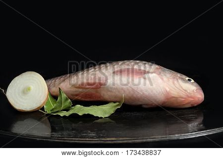 Raw freshwater fish on the table and a black background.Place for text.
