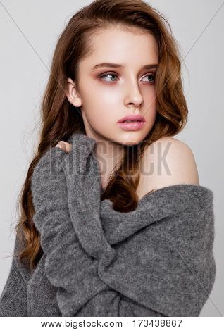 Young beautiful fashion model wearing knitwear jumper on grey background