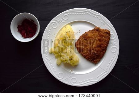 Pork fried schnitzel with  potato on black wooden table. Wiener schnitzel