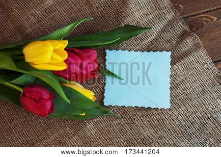 Spring flowers on sacking and a welcome card. Concept of holiday birthday Easter March 8.