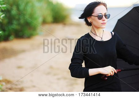 Beautiful young brunette girl in black clothes with a large black umbrella on the shore of the Bay the cool summer day.