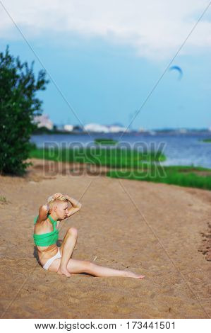 young blonde girl doing yoga exercises on the beach near the water