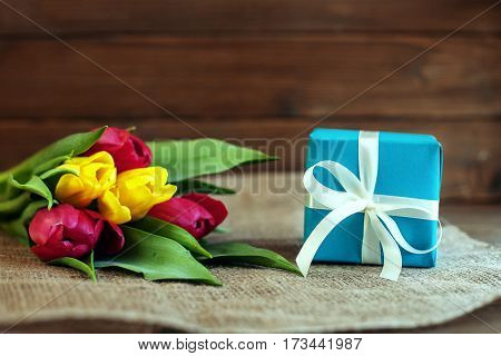 Tulips and gift. Greeting. Concept of holiday birthday Easter March 8.