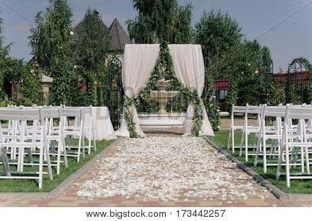 Beautiful wedding archway. Arch decorated with biege cloth and flowers, outdoor