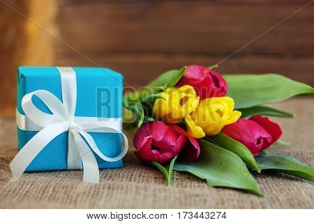Beautiful tulips and blue gift. Greeting. Concept of holiday birthday Easter March 8.