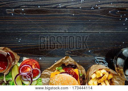 Fresh Delicious Burgers With French Fries, Sauce And Drink On The Wooden Table Top View, With Copy S