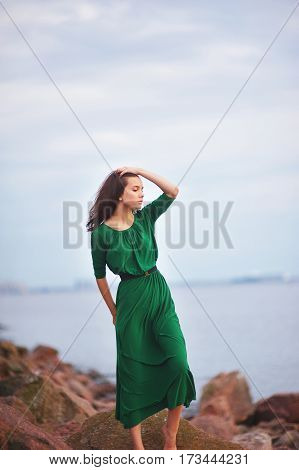 beautiful woman in a green dress looks at the evening sun. she stands barefoot on the rocks by the sea.