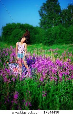 Beautiful brunette girl with a tattoo on the foot is on the trolley in the field and waving hair. wearing a white T-shirt and short denim shorts. Field dotted with the violet flowers of willow-herb.