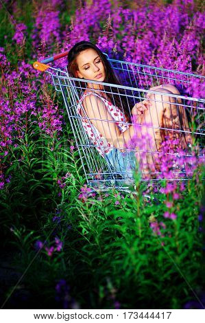 Beautiful brunette girl sitting on the trolley in the field. She is wearing a white T-shirt and short denim shorts. Field dotted with the violet flowers of willow-herb.