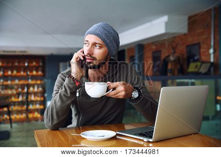 Young handsome hipster man with beard sitting in cafe talking mobile phone, holding cup of coffee. Laptop on wooden table