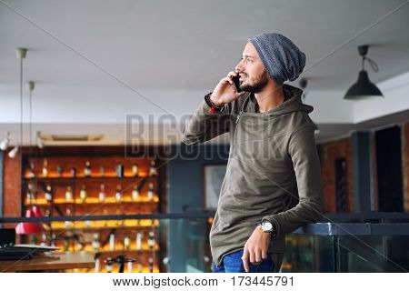 Young handsome man using smartphone in cafe