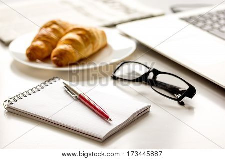 Office breakfast with newspaper, croissant and laptop on white desk