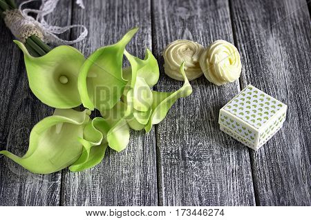 Bouquet Of Green Yellow Calla Lilies With Cardboard Box And Marshmallows On A Gray Wooden Background